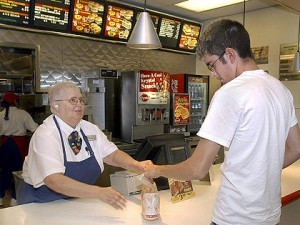 Elderly lady serving in fast food chain